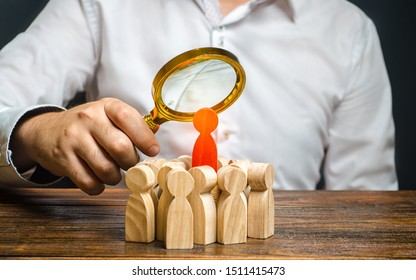 A man is studying the red figure of a man at the head of a crowd. Identify disloyal, repression, dissent. toxic, non-competent worker. Search for the organizer and leader of the protests. Crime.