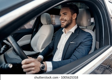 Man of style and status. Handsome young man in full suit smiling while driving a car