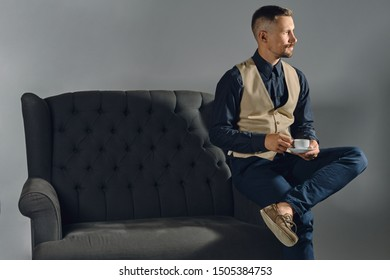 Man with stylish mustache, dressed in black shirt and trousers, beige vest is sitting on dark sofa, holding cup of coffee. Grey background, close-up.