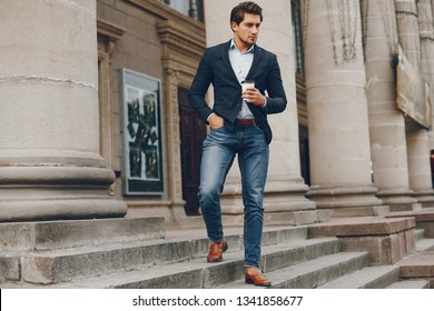 Man in a stylish suit. Businessman in a summer city. Male drinking a coffee