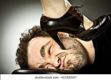 man submission with woman high heel shoe on grey background