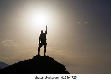 Man success with arms outstretched celebrating or praying in beautiful inspiring mountains sunrise, silhouette. Man hiking or climbing with hands up enjoy inspirational landscape on rocky Crete.