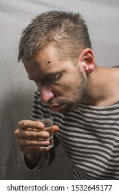 A man suffering from alcoholism drink vodka at home alone, action against alcohol.