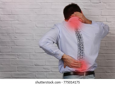 Man suffering from back and neck pain. Incorrect sitting posture problems, Muscle spasm, rheumatism. Pain relief , chiropractic concept.