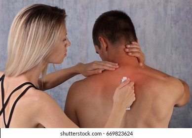Man suffering from back pain,woman applying pain relief cream on man's back, Sport couple