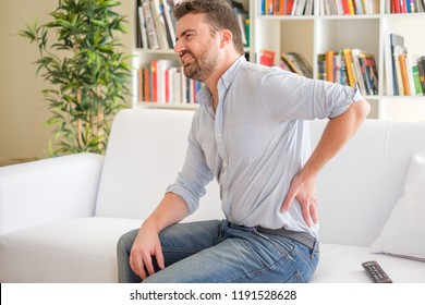 Man suffering backache seated on the sofa
