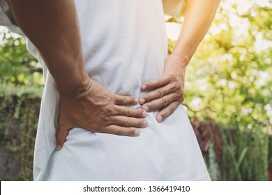 A man suffering from backache, spinal injury and muscle issue problem at outdoor.