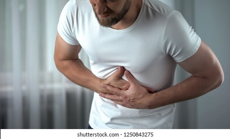 Man suffering bellyache at home, gastritis symptom, peptic ulcer, pancreatitis