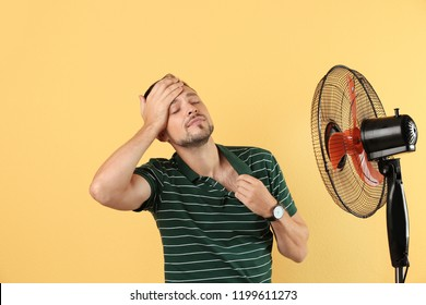 Man suffering from heat in front of fan on color background
