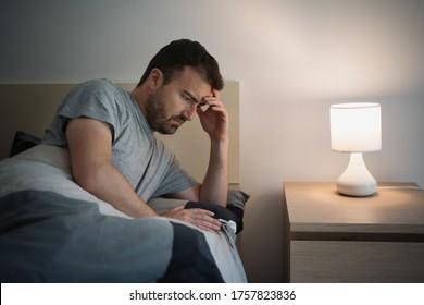 Man suffering insomnia having problems falling asleep
