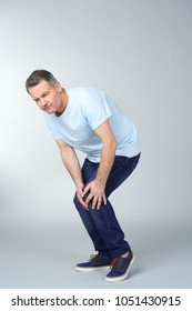 Man suffering from knee pain on light background