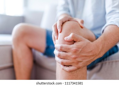 Man suffering from knee pain sitting sofa. A mature man massaging his painful knee. Man suffering from knee pain at home, closeup. Pain knee