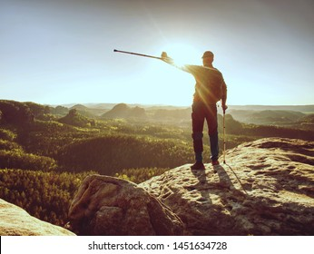 Man Suffering Leg Injury on Mountain Hike. Disabled man with crutches stands on a big rock and looking to mountains at horizon