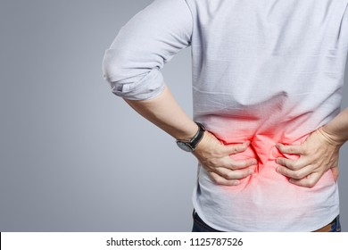 Man suffering from a lower back pain on grey background