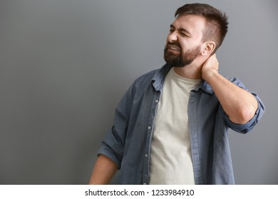 Man suffering from neck pain on grey background