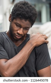 man suffering from neck pain; sick african man with neck joint pain, osteoporosis, bone arthritis, gout, symptoms; body sickness, health care or pain concept; adult african man or black man model