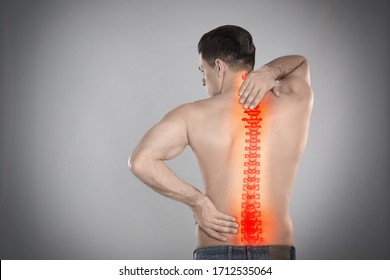 Man suffering from pain in spine on grey background