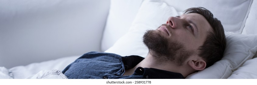 Man suffering from sleeplessness lying with open eyes