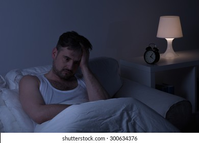 Man suffering from sleeplessness sitting in the bed