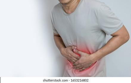 Mann mit Magenschmerzen mit beiden Handflächen um die Weste, um Schmerzen und Verletzungen auf der Bauchfläche zu zeigen