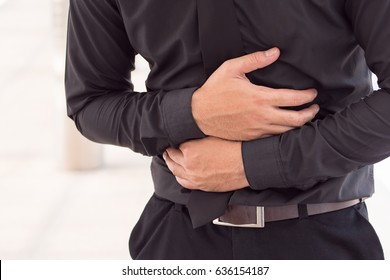 man suffering from stomach ache, diarrhea, constipation, acid reflux, indigestion, nausea