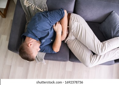 Man Suffering From Stomach Ache Lying On Sofa