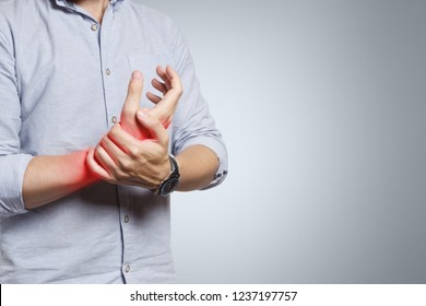 Man suffering from wrist pain on grey background