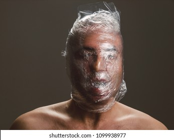 Man suffocating with plastic around his head, isolated on dark background