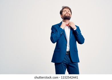 a man in a suit adjusts a bow tie around his neck