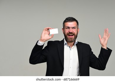 Man in suit with beard holds white business card. Guy with happy face and glasses on grey background. Businessman with empty card, copy space. Business and success concept
