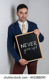 Man in a suit with a black board in his hands on a white background. Motivation text never give up.