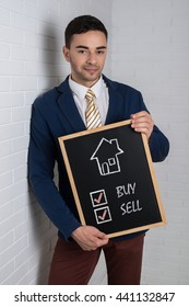 Man in a suit with a black board in his hands on a white background. Drawn the house and motivational text.