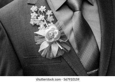 A man in a suit with a bow pinned to the chest wedding