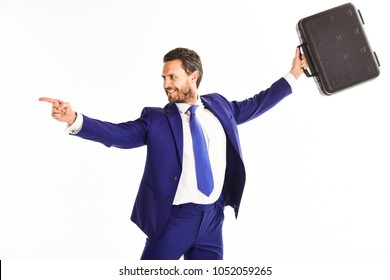 Man in suit or businessman with happy face holds briefcase on white background. Businessman raises up briefcase above his head and points to opposite side with index finger. Business success concept.