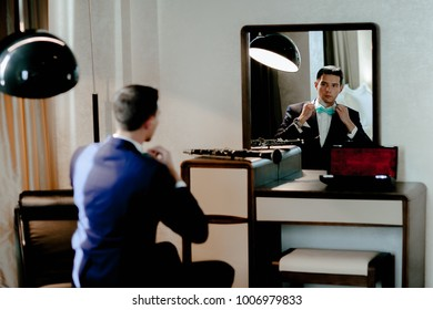 a man in a suit with a butterfly with a serious view is looks in the mirror and corrects the butterfly
