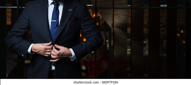 Man in suit buttoning his jacket