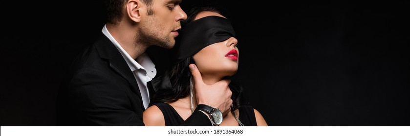 man in suit choking blindfolded woman with silk ribbon on eyes isolated on black, banner