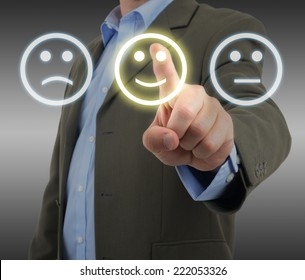 Man in suit choosing a smiley face on a survey panel