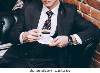 A man in a suit with a cup of coffee sits on a black leather sofa