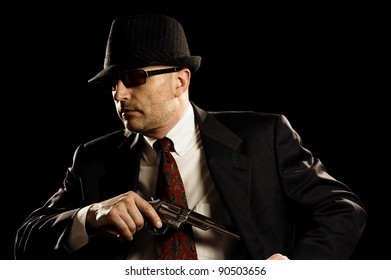 Man in suit draws antique handgun, mobster style outfit.