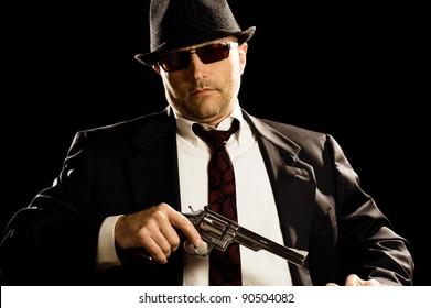 Man in suit draws vintage handgun, white collar outfit.
