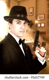 Man in suit draws vintage handgun, white collar outfit.