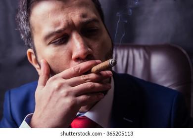 Man in suit dress smoking a cuban cigar.Black background.Black background