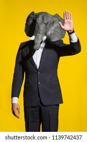 A man in a suit and an elephant mask on a yellow background. Conceptual business background