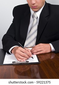 Man in suit filling out a form on a clipboard