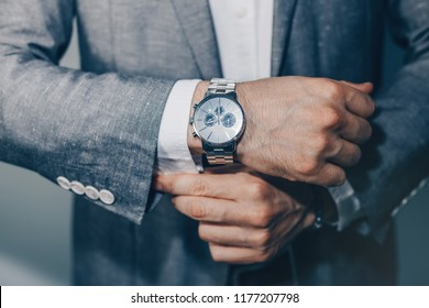 Man in suit fixing his cufflinks. watch in a man