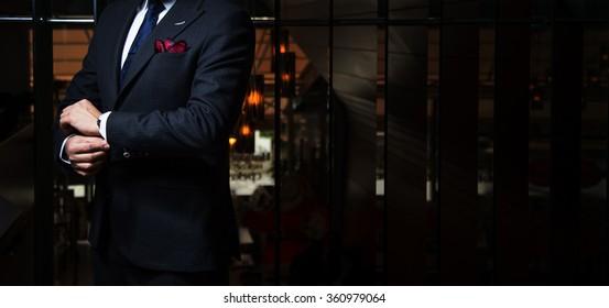 Man in suit fixing his cufflinks