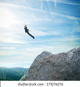 Man in suit flying over mountains