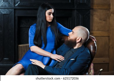 A man in a suit and a girl in a dress. A bearded guy sits on a chair with a beautiful girl. A girl in a blue dress with a bearded man