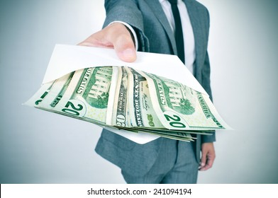 a man in suit giving an envelope full of american dollar bills